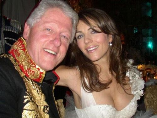 """Bin Clinton và """"bông hồng nước Anh"""" Elizabeth Hurleychụp ảnh chung một cách thân thiện trong dạ hội hóa trang từ thiện ở Nga năm 2005"""