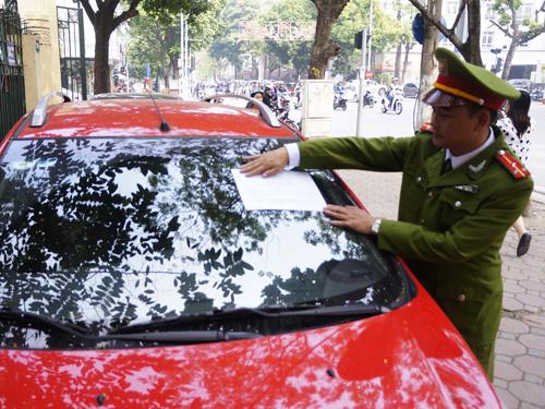 Lực lượng công an quận Hoàn Kiếm đồng loạt ra quân dán thông báo vi phạm lên kính xe ô tô đỗ trên vỉa hè - Ảnh: Phú Xuân