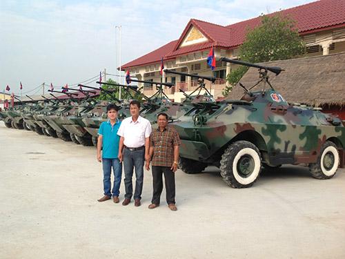 Ông Trần Quốc Hải (giữa) bên những chiếc xe bọc thép do ông sáng chế cho Campuchia Ảnh: LÂM NGỌC
