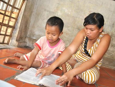 Em Nguyễn Tấn Bo đọc sách cho mẹ nghe