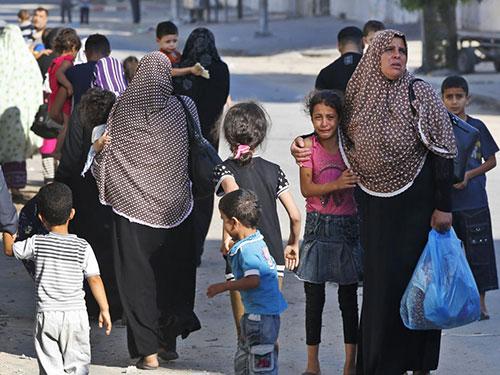 Người dân vùng ngoại ô thành phố Gaza rời khỏi nhà hôm 16-7 Ảnh: AP