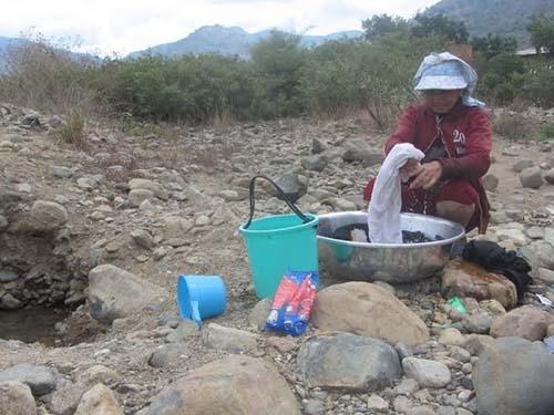 Người dân xã Hàm Cần, huyện Hàm Thuận Nam, tỉnh Bình Thuận đào hố dưới sông vét từng ca nước Ảnh: Bạch Long