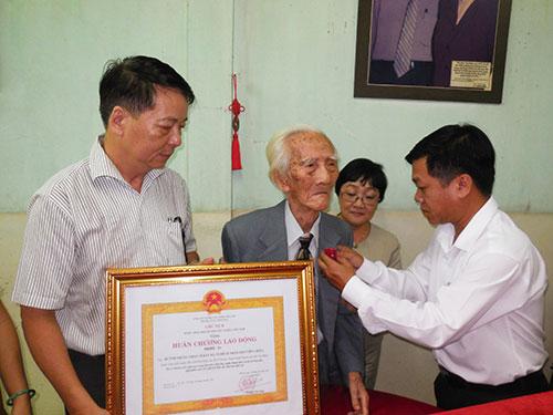 Ông Nguyễn Văn Minh - Phó Giám đốc Sở VH, TT và DL TPHCM trao Huân chương lao động hạng ba cho NSND NSND Bảy Bá - soạn giả Viễn Châu Ảnh: Thanh Hiệp