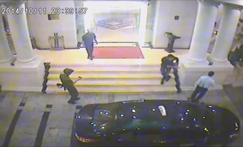 Hình ảnh từ camera ngoài cửa khách sạn cho thấy có người mặc sắc phục công an, tay cầm súng