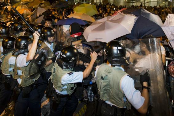 Người biểu tình che dù để tránh hơi cay. Ảnh: Reuters