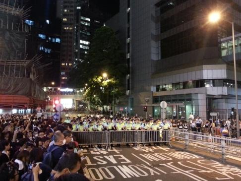 Người biểu tình và cảnh sát trước trụ sở cảnh sát quận Loan Tử. Ảnh: SCMP