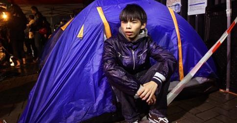 Joshua Wong ngồi dưới cơn mưa đêm 1-12. Ảnh: SCMP