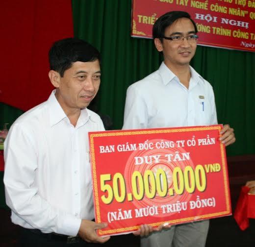 Đại diện Công ty CP sản xuất Nhựa Duy Tân (bìa phải) trao tiền ủng hộ chương trình hỗ trợ công nhân nâng cao trình độ cho ông Nguyễn Văn Hạnh, nguyên chủ tịch LĐLĐ quận Bình Tân