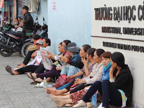 Phụ huynh vạ vật chờ con trước cổng Trường ĐH Công nghiệp, TP HCM. Ảnh: Đ. Trinh