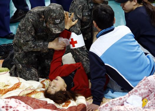 South Korean medics help a collapsed family member of a missing passenger who was on South Korean ferry Sewol which sank in the sea off Jindo, as she cries while waiting for news from a rescue team, at a gym in Jindo April 18, 2014. REUTERS-Kim Kyung-Hoon