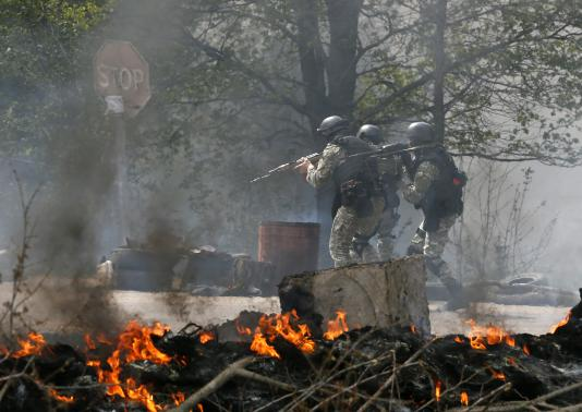Ukrainian security force officers walk past a checkpoint set on fire and left by pro-Russian separatists near Slaviansk April 24, 2014. REUTERS-Gleb Garanich