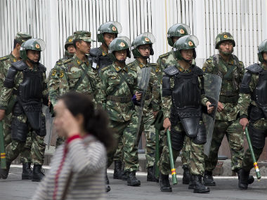 Paramilitary policemen with shields and batons patrol near the Peoples Square in Urumqi, Chinas northwestern region of Xinjiang. AP