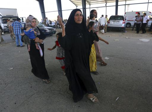 A woman reacts as families fleeing the violence in the Iraqi city of Mosul arrive at a checkpoint on the outskirts of Arbil, in Iraqs Kurdistan region June 10, 2014. REUTERS-Stringer