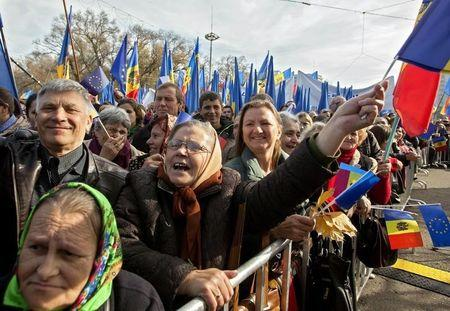 People wave EU and Moldavian national flags, and shout slogans, during a pro-EU rally in Chisinau,