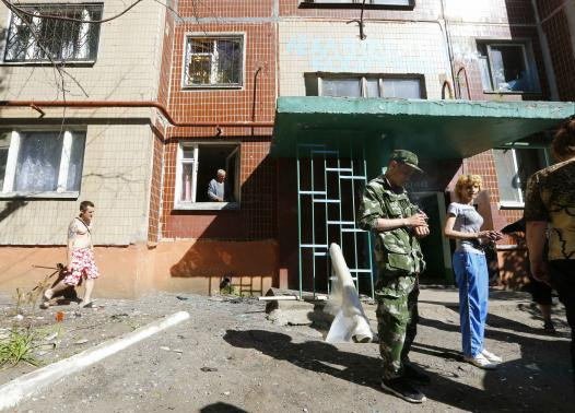 Local residents and a pro-Russian fighter stand near the entrance to an apartment block damaged by shelling in Slaviansk in eastern Ukraine June 29, 2014.REUTERS-Shamil Zhumatov