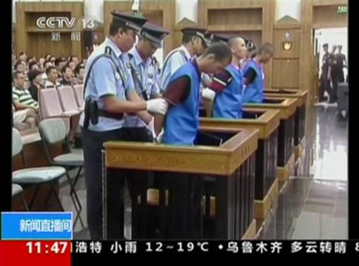 Defendants are escorted by police officers at a courtroom in Kunming City during the trial of four people accused of participating in an attack at a train station in southwestern China, in this still image taken from video September 12, 2014.  REUTERS-CCTV via Reuters TV