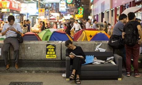 Một người đàn ông nghỉ bên cạnh một đống báo trên đường Nathan. Ảnh: EPA