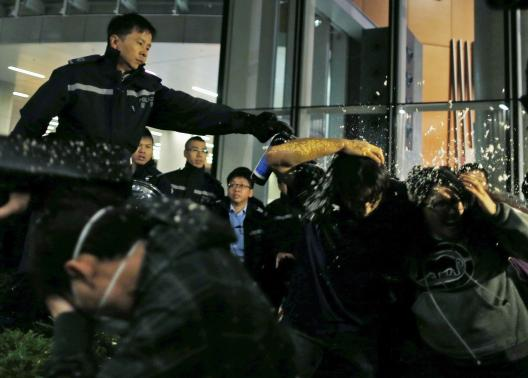Pro-democracy protesters are pepper sprayed by a policeman as they try to break into the Legislative Council in Hong Kong early November 19, 2014, in response to an earlier clear up by bailiffs on part of the Occupy Central protest site.  REUTERS-Tyrone Siu