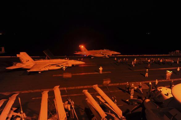 2 chiếc F-18 chuẩn bị cất cánh từ tàu sân bay USS George H.W. Bush tối 22-9. Ảnh: REUTERS