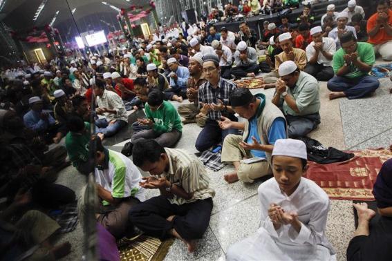Người dân Malaysia cầu nguyện ngay sảnh vào của sân bay quốc tế Kuala Lumpur. Ảnh: Reuters