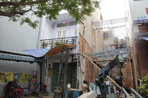 Hiện trường căn nhà số 97 bị nghiêng và lún sang một bên được cơ quan chức năng dùng những thanh sắt chống, ngăn không bị đổ