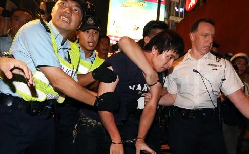Một người bị bắt ở khu Vượng Giác. Ảnh: SCMP
