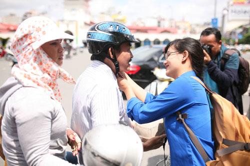 Thanh niên tình nguyện đang cài mũ bảo hiểm đạt chuẩn cho người dân.