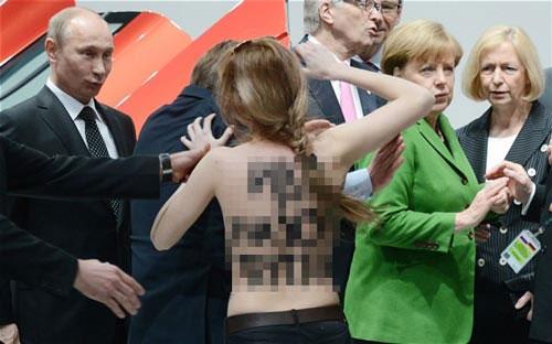 """Biểu cảm thú vị trên khuôn mặt của ông Putin khi """"chạm mặt"""" một phụ nữ ngực trần biểu tình ở Đức  hôm 8-4. Ảnh: Telegraph"""