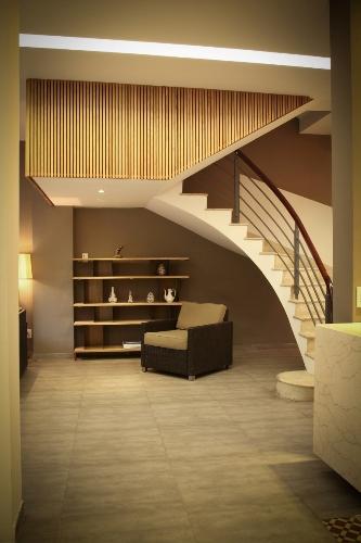 Sau cải tạo, chủ nhà có thể bố trí chỗ ngồi thư giãn dưới cầu thang uốn lượn mềm mại.