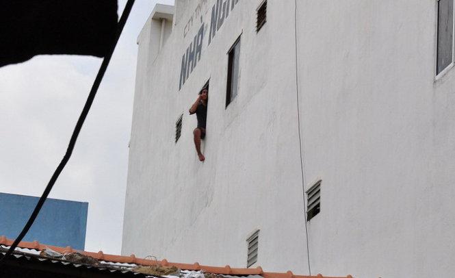 Nam thanh niên đang ngồi ở tầng 3 của nhà nghỉ Trùng Dương đòi nhảy lầu tự tử - Ảnh: Tấn Vũ