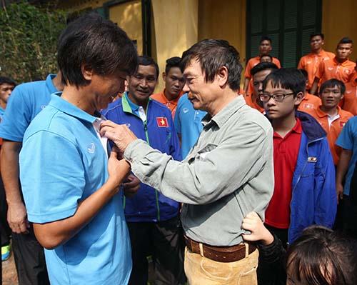 Ông Võ Điện Biên (bìa phải) trao huy hiệu cho HLV Miura Toshya