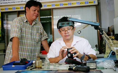 Anh Quý (đứng) và em trai là Tuấn đang trao đổi công việc - Ảnh: Tuyển Nguyễn