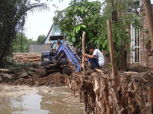 Bà Nguyễn Thị Nụ thuê máy xúc móc đất đã lấp rạch từ năm 2003 để trả lại sự thông thoáng cho dòng chảy