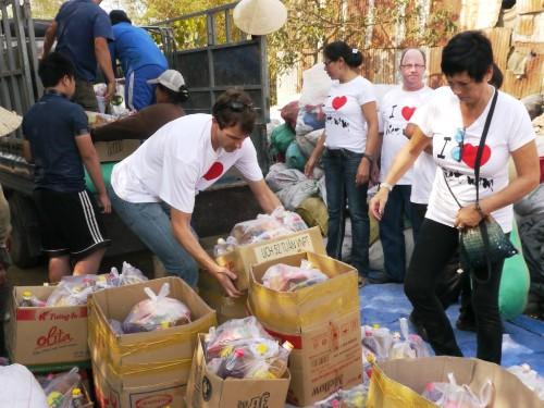 Nhóm người nước ngoài đưa quà Tết xuống xe để phát cho người dân nhặt rác
