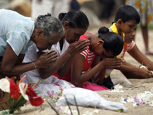 Người thân những nạn nhân sóng thần cầu nguyện gần một ngôi mộ tập thể ở Pereliya - Sri Lanka hôm 26-12Ảnh: Reuters