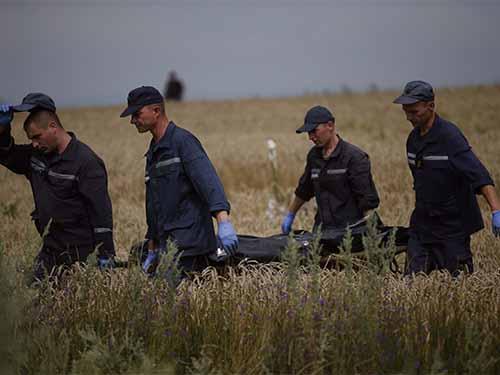 Các nhân viên cứu hộ Ukraine khiêng thi thể nạn nhân tại hiện trường vụ rơi máy bay hôm 19-7 Ảnh: Reuters