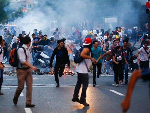 Người biểu tình chống chính phủ bị bắn hơi cay tại Caracas - Venezuela hôm 12-2Ảnh: Reuters