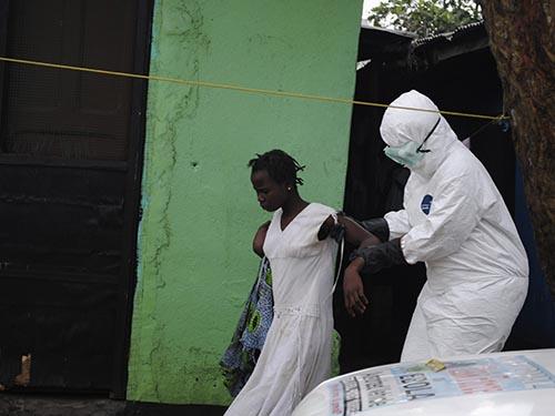 Nhân viên y tế đưa một phụ nữ nghi nhiễm virus Ebola tới xe cứu thương tại LiberiaẢnh: Reuters