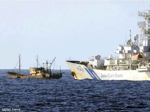Tàu tuần tra Nhật Bản (phải) ngăn chặn tàu cá Trung Quốc ở ngoài khơi đảo YomejimaẢnh: Japan News