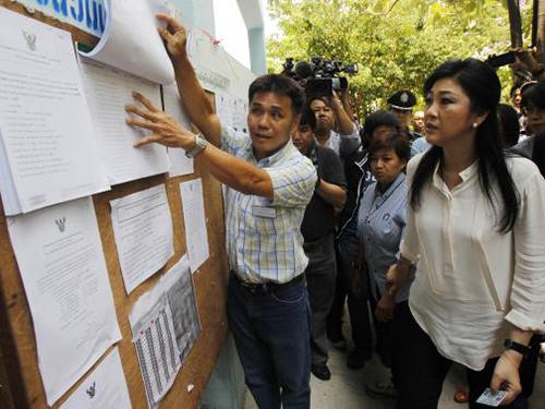 Thủ tướng Thái Lan Yingluck Shinawatra (phải) kiểm tra danh sách cử tri trước khi bỏ phiếu tại Bangkok ngày 30-3Ảnh: REUTERS