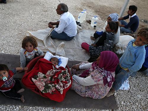 Một gia đình người Kurd chạy khỏi TP Kobani do chiến sự leo thang ở đó Ảnh: Reuters