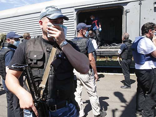 Người dân và quan sát viên Tổ chức An ninh và Hợp tác châu Âu (OSCE) đứng trước một toa tàu đông lạnh chứa thi thể nạn nhân hôm 21-7Ảnh: REUTERS