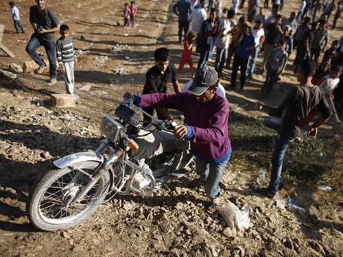 """Một người Kurd ở Syria """"ôm"""" xe trốn chạy sang Thổ Nhĩ Kỳ Ảnh: REUTERS"""