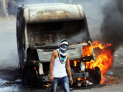 Người biểu tình Palestine đốt xe của người Israel trong cuộc đụng độ ở Đông Jerusalem hôm 30-10 Ảnh: Reuters
