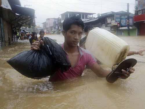 Người dân thủ đô Manila cố gắng lội qua con đường ngập sâu Ảnh: AP