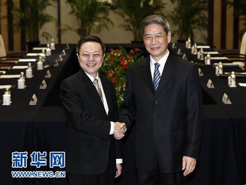 Ông Trương Chí Quân (phải) và ông Vương Úc Kỳ bắt tay trước buổi họp ngày 11-2Ảnh: TÂN HOA XÃ