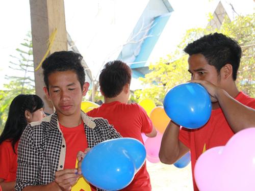 Hồng Duy (trái) thổi bong bóng tặng các em nhỏ