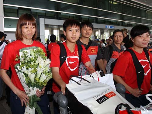 Thủ môn Kiều Trinh (bìa trái) và các đồng đội về đến sân bay Tân Sơn Nhất trưa 9-5 sau đợt tập huấn  tại Trung Quốc và Hàn Quốc