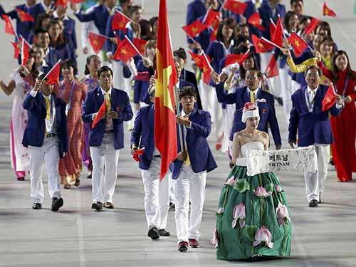 Kình ngư Hoàng Quý Phước cầm quốc kỳ cho đoàn Việt Nam trong lễ diễu hành đêm khai mạcẢnh: REUTERS