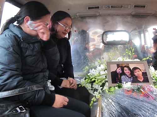 Gia đình bên linh cữu của 3 mẹ con chị Minh tại sân bay Nội Bài